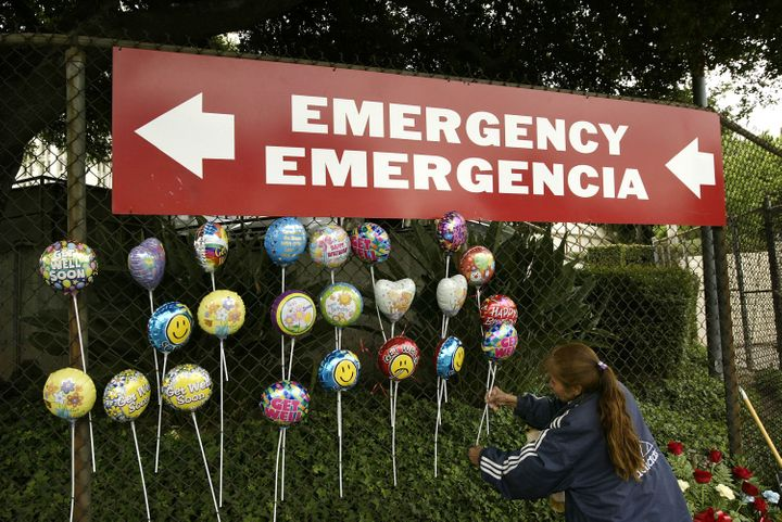 LOS ANGELES - MAY 17:  A Mexican immigrant arranges 'get well' balloons she is selling under a sign pointing to the emergency