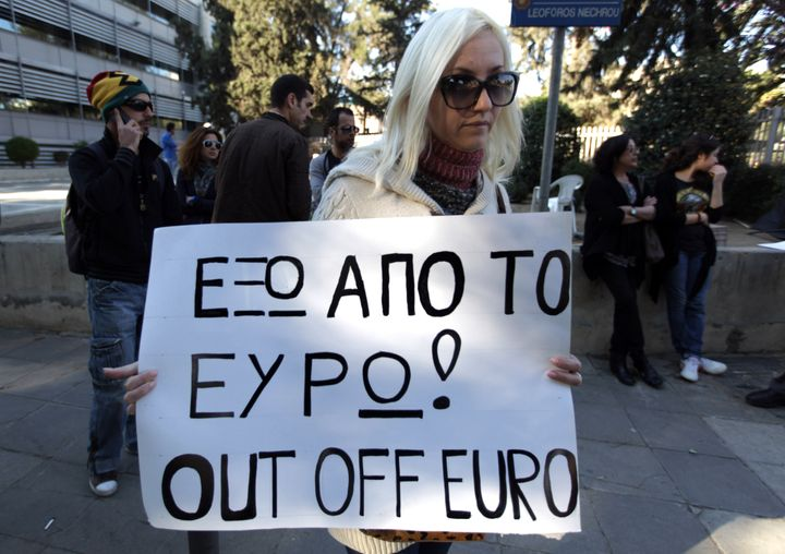 A Russian woman holding dual nationality holds a placard during a protest outside the parliament in Nicosia on March 24, 2013
