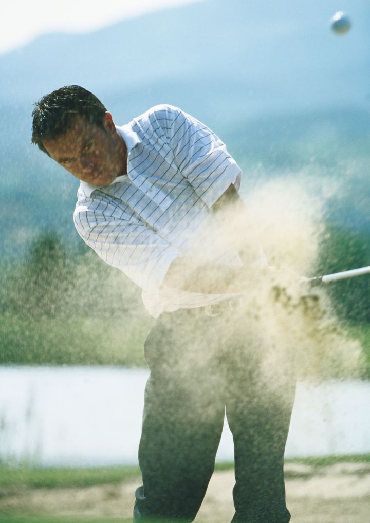 Golfer, mid-swing in sand trap, with sand in mid-air