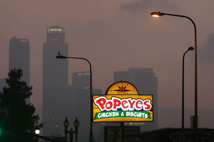 LOS ANGELES, CA - JULY 24: A Popeyes fast-food restaurant sign glows above the city skyline on July 24, 2008 located in the F