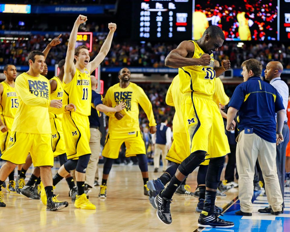 Michigan players including Time Hardaway Jr., right, and Nik Stauskas (11) celebrate after defeating Syracuse in their NCAA F
