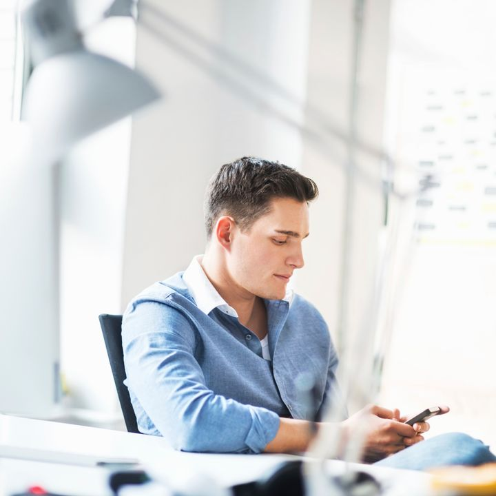 Young casual businessman sitting on his desk and texting on smart phone