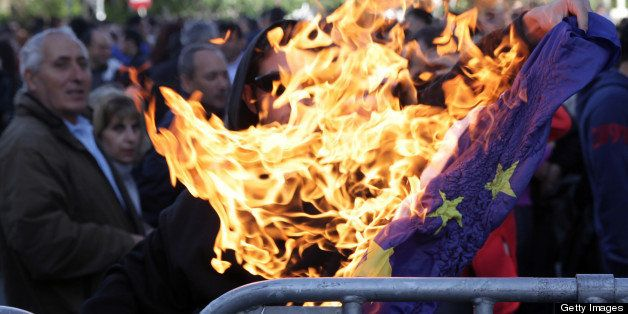 A demonstrator burns a European Union flag outside the parliament in the Cypriot capital, Nicosia, on April 4, 2013, followin
