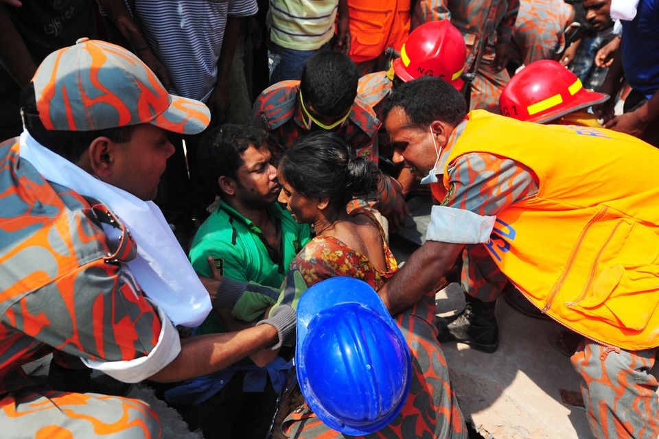 Bangladeshi firefighters rescue a garment worker (C) found alive in the collapse of an eight-storey building in Savar, on the