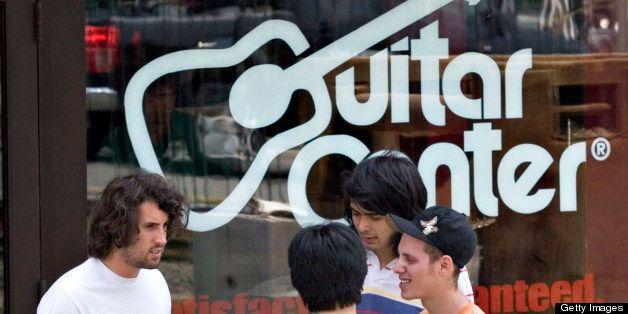 UNITED STATES - JUNE 27:  Guitar Center employee Josh Weinhaus, back to camera, talks with customers Chris Villano, left, Pau