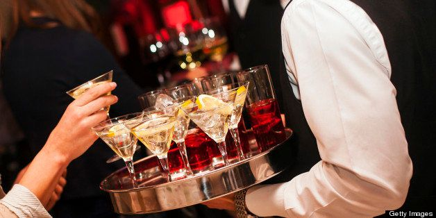 Waiter holding a tray full with Martini coctails