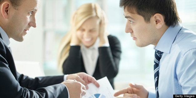 Two business partners arguing over papers with growing passion