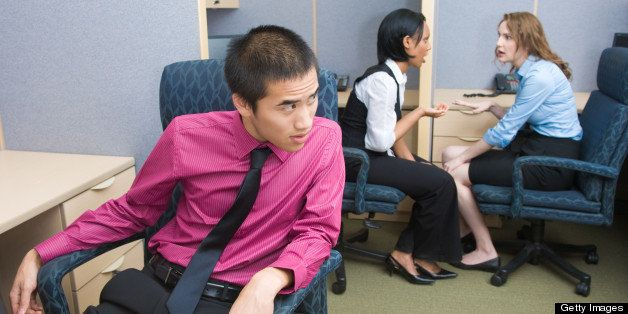 2 female coworkers gossiping while another coworker eavesdrops.