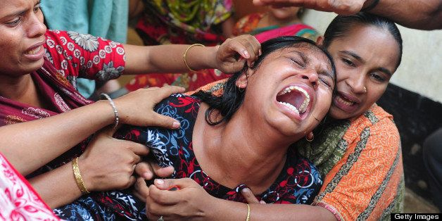 Relatives react after identifying the body of a loved one killed in last week's building collapse in Savar, on the outskirts
