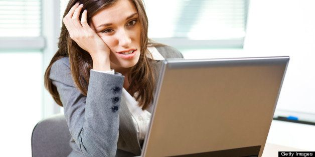 Young woman looking at the computer and boring or not happy about the news.