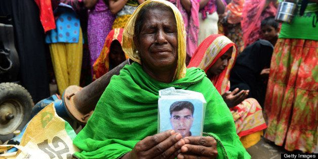 A Bangladeshi family member holds up the portrait of her missing relative as she offers prayers in front of the rubble of a n