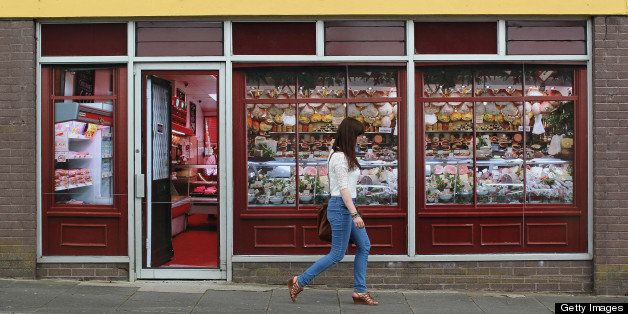 A pedestrian walks pass stickers applied to the windows of a former butcher?s shop in Belcoo, Northern Ireland, outside Ennis