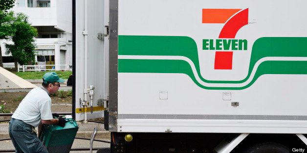 A delivery driver loads crates onto a Seven & I Holdings Co. truck displaying the 7-Eleven logo in Kawasaki City, Kanagawa Pr