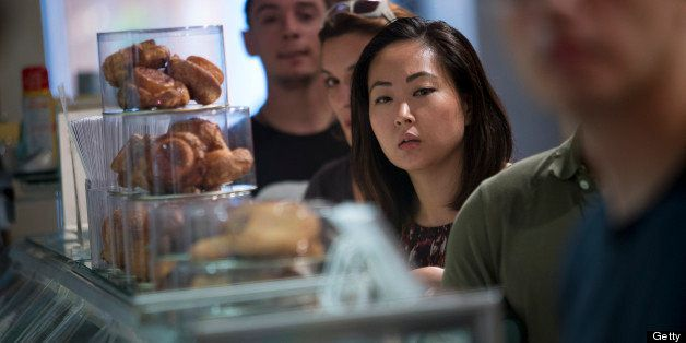 Customers wait in line to make purchases at the Dominique Ansel Bakery in New York, U.S., on Thursday, June 27, 2013. Custome