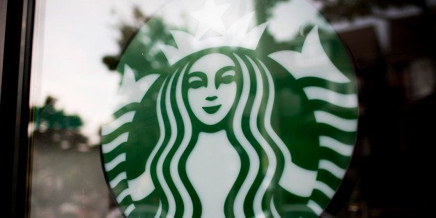 The Starbucks Corp. logo is displayed in the window of a store in Toronto, Ontario, Canada, on Tuesday, July 23, 2013. Starbu