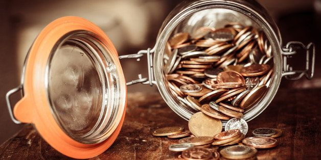 A jar of sterling coins is tipped on its side with the coins spilling out on to a wooden surface. The jar denotes a savings p