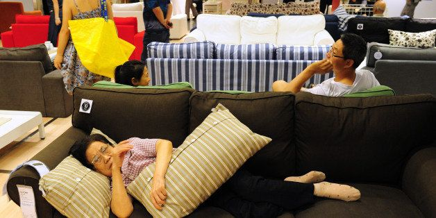An elderly Chinese (bottom) women rests on a sofa as people shop at an Ikea frurniture store in Beijing on August 15, 2011. A