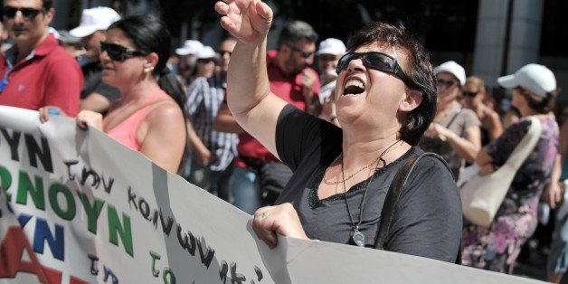 An employee shouts towards the ministry of labour in Athens during a protest march by civil servants on August 5, 2013. Greec