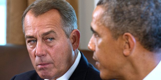 Speaker of the House John Boehner (L), R-OH, listens as US President Barack Obama delivers a statement on Syria during a meet