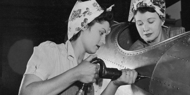circa 1943:  One American female worker drives rivets into an aircraft while another sits in the cockpit on the US home front