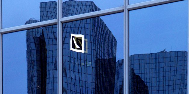 The Deutsche Bank AG headquarters are reflected in the window of a building in Frankfurt, Germany, on Monday, Jan. 30, 2012.