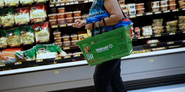 A customer carries a shopping basket during the grand opening of a Wal-Mart Stores Inc. location in the Chinatown neighborhoo