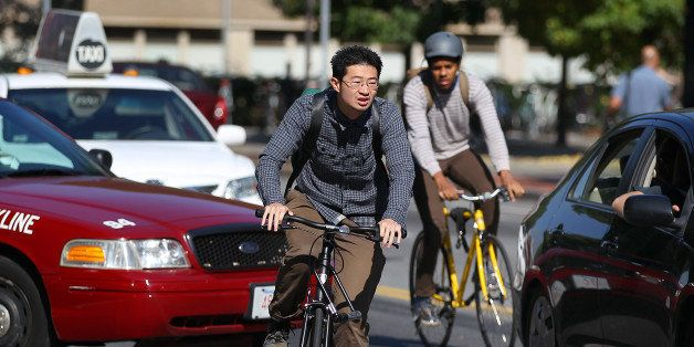 CAMBRIDGE, MA - OCTOBER 5: Two bicyclists weave through traffic near MIT, one of whom is not wearing a helmet. (Photo by John
