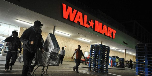 Shoppers wheel their purchases out of a Wal-Mart store in Los Angeles, California, before dawn on Black Friday, November 27,