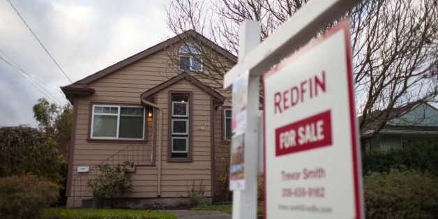 A Redfin Corp. 'For Sale' sign stands outside of a home in Seattle, Washington, U.S., on Tuesday, Nov. 19, 2013. Purchases of
