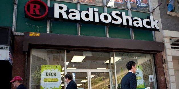 Pedestrians pass in front of a RadioShack Corp. store in New York, U.S., on Thursday, Oct. 24, 2013. RadioShack Corp.'s new f