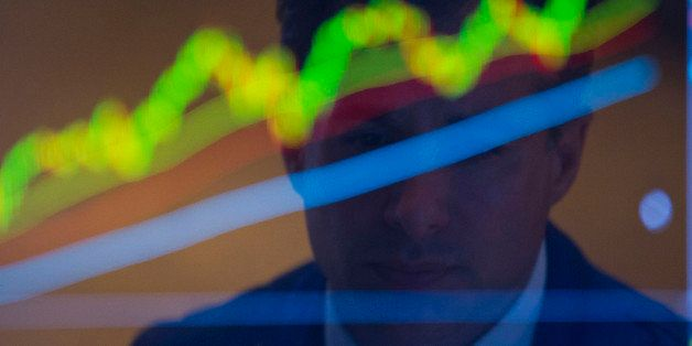 The reflection of a trader working is seen on a monitor on the floor of the New York Stock Exchange (NYSE) in New York, U.S.,