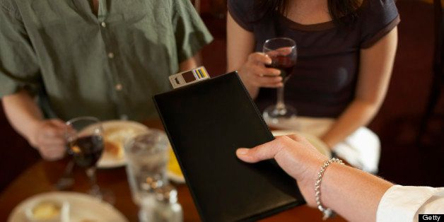 Waitress handing bill to couple in restaurant