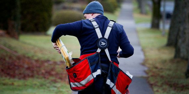 A Canada Post letter carrier puts packages in a bag while delivering mail by foot to houses in Vancouver, British Columbia, C