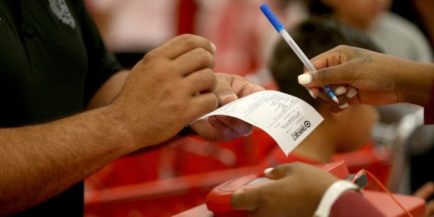 MIAMI, FL - DECEMBER 19:  A customer prepares to sign a credit card slip at a Target store on December 19, 2013 in Miami, Flo