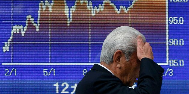 A pedestrian walks past an electronic stock board displaying a graph of the 12-month movement of the exchange rate of the yen