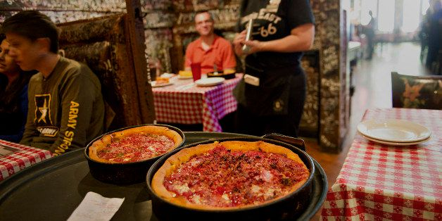 A waitress carries deep dish pizzas to customers at Gino's East restaurant in Chicago, Illinois, U.S., on Wednesday, April 18