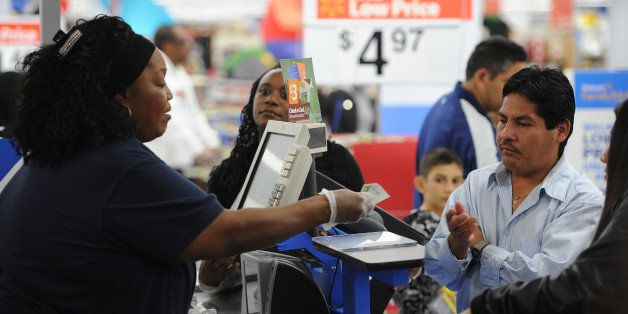 An employee rings up sales at a cash register at a  Walmart in the Crenshaw district of Los Angeles on Black Friday, November