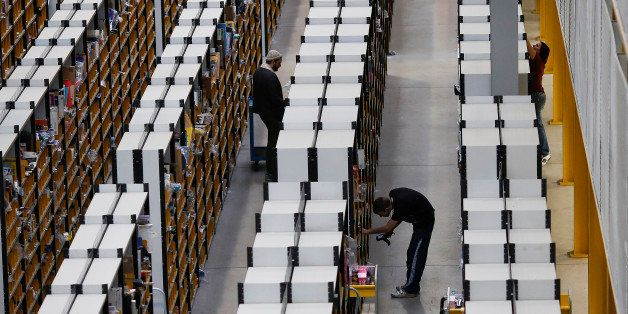 Employees process customer orders ahead of shipping at one of Amazon.com Inc.'s fulfillment centers in Rugeley, U.K., on Mond