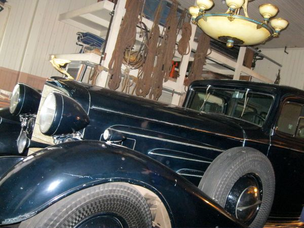 A 1933 Cadillac V-16 seven-passenger limousine with golden goddess hood ornament remains under an ornate chandelier inside th