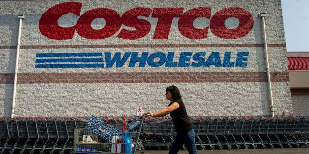 A customer pushes a cart of purchased items outside a Costco Wholesale Corp. store in Hackensack, New Jersey, U.S., on Wednes