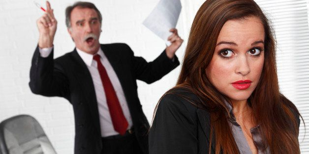 Female business secretary with his angry boss with documents in the back.