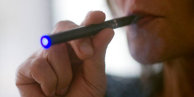 This September 25, 2013 photo illustration taken in Washington, DC, shows a woman smoking an 'Blu' e-cigarette (electronical