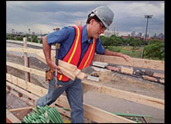 Mitt Romney dressed as a construction worker moves 2x4's.