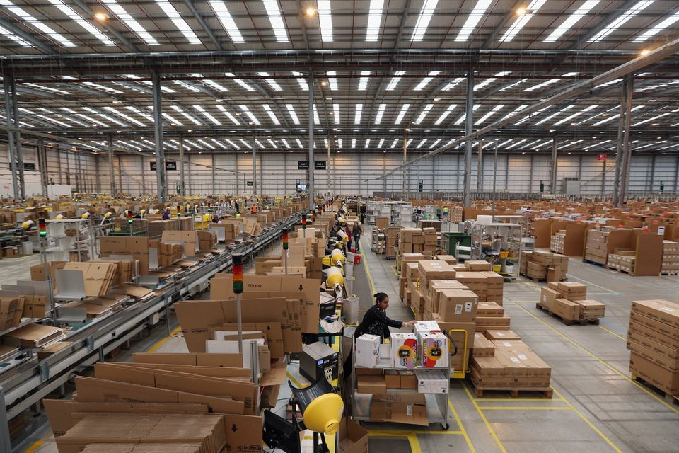 PETERBOROUGH, ENGLAND - NOVEMBER 28:  Employees select and dispatch items in the huge Amazon 'fulfilment centre' warehouse on