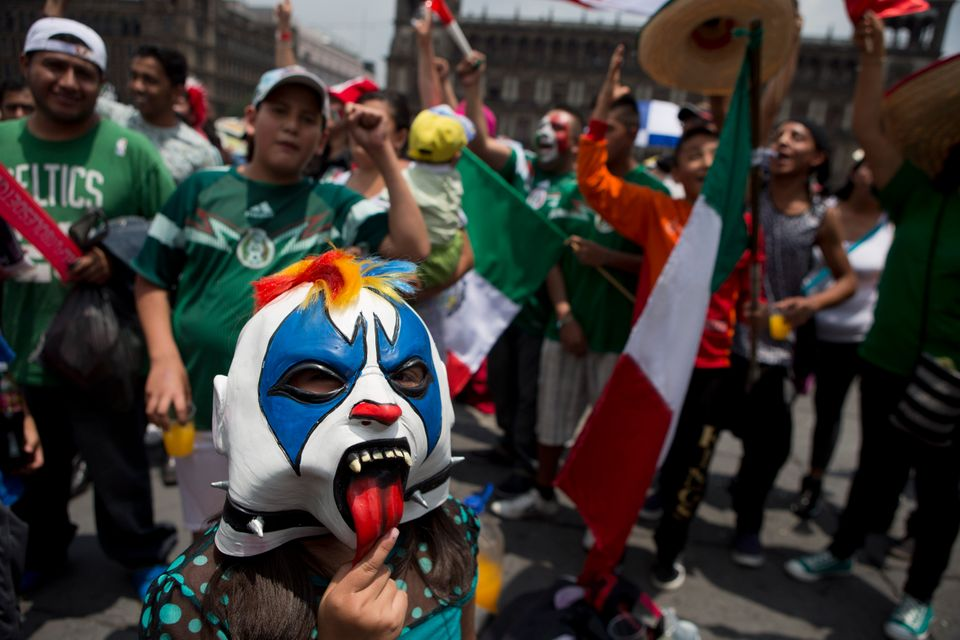 A masked girl poses for photo surrounded by Mexico soccer fans as they watch their team's World Cup match with Brazil on gian