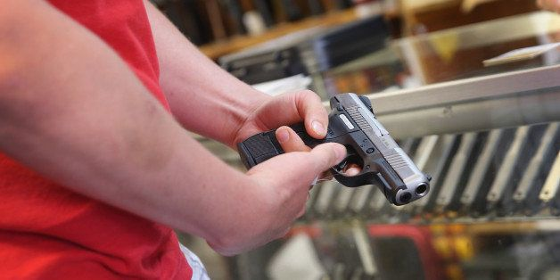 TINLEY PARK, IL - JUNE 16:  A customer shops for a handgun at Freddie Bear Sports on June 16, 2014 in Tinley Park, Illinois.