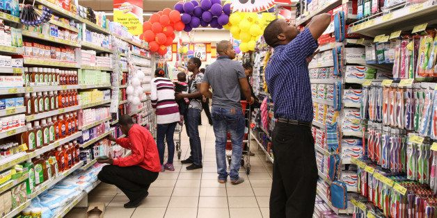 Employees restock shelves with pharmaceutical products inside a Shoprite Holdings Ltd. supermarket in Johannesburg, South Afr
