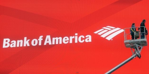 Workers fix a large electronic billboard featuring an advertisement for Bank of America on Times Square in New York, February