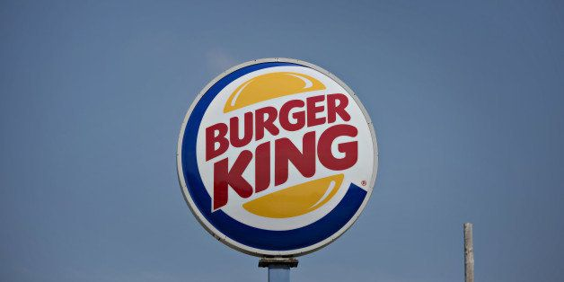 Burger King Worldwide Inc. signage stands outside a restaurant in Peoria, Illinois, U.S., on Tuesday, Aug. 26, 2014. Burger K