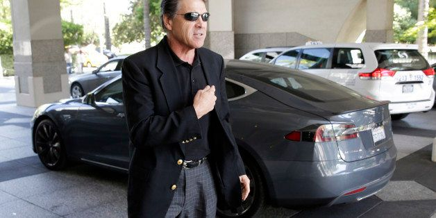 Texas Gov. Rick Perry walks over to talk to reporters after driving up in a Tesla Motors Type S electric car in Sacramento, C